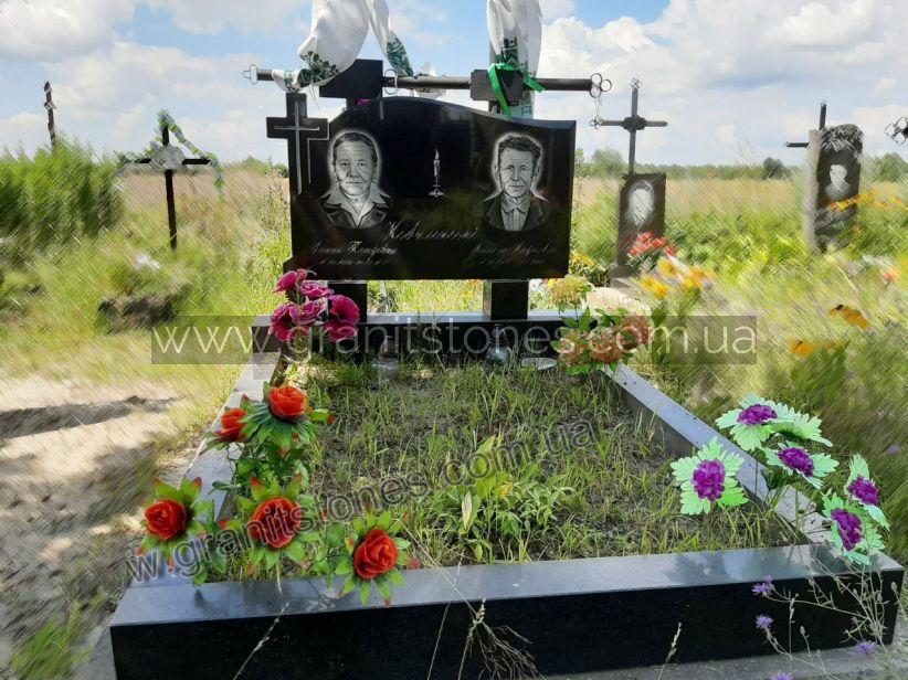 Гранитный памятник черного цвета с большим цветником
