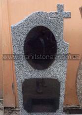 Памятник из серого камня с небольшим крестом