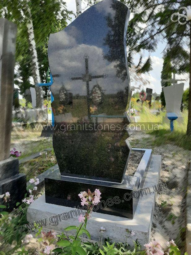 Гранитный памятник черного цвета с небольшим цветником